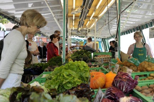Kunden an einem der vielen Gemüsestände suchen sich ihre Waren aus.